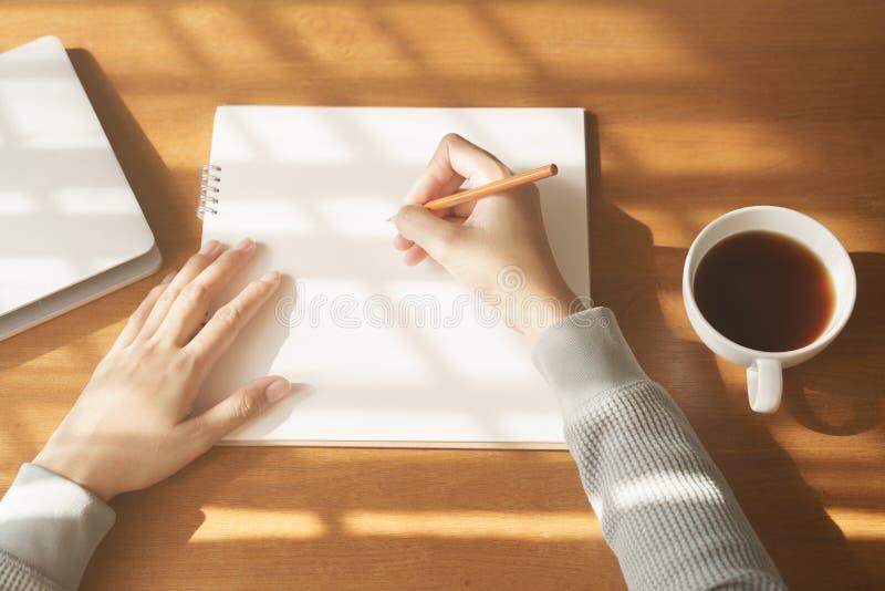 handkvinna som skriver anteckningsboken P? tr?skrivbordbakgrund ha den kaffekoppen och b?rbara datorn i morgonljus royaltyfri bild