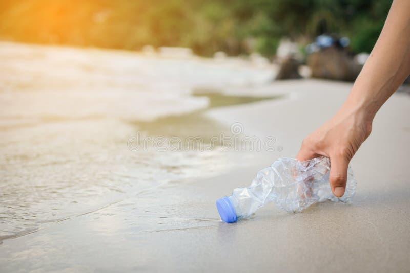 Handkvinna som upp väljer plast- flasklokalvård på stranden royaltyfria bilder