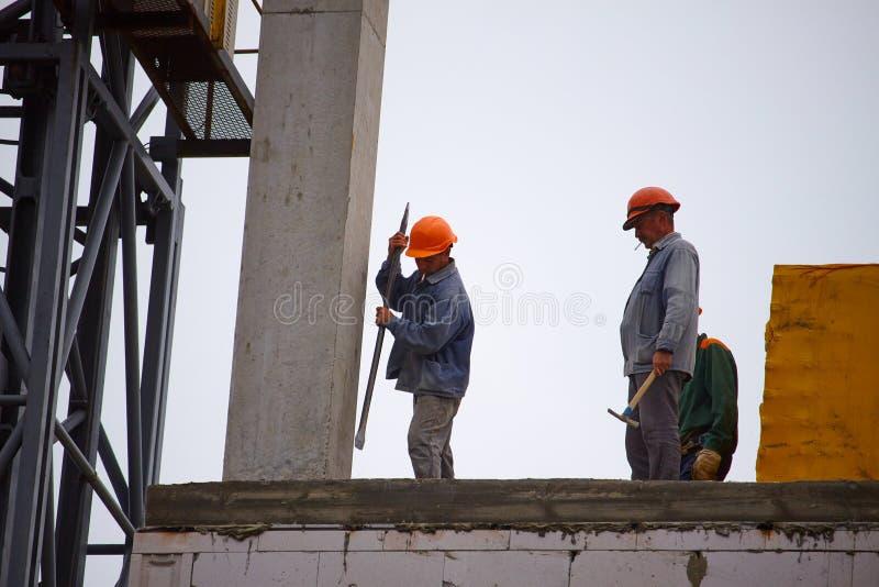 Handläggare arbetar med att bygga en cementbyggnad med flera våningar, att bilda cementstöd i monteringsfärdiga former arkivfoto