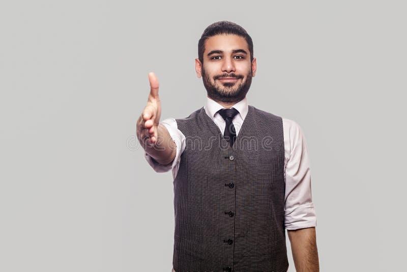 Handla, handskakning och hälsning Stående av den lyckliga stiliga skäggiga brunettmannen i det vita skjorta- och waistcoatanseend arkivfoton