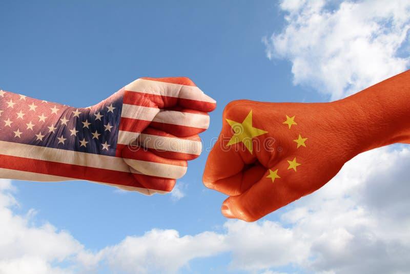 Handla konflikten, nävar med flaggorna av USA och Kina mot ea arkivfoto