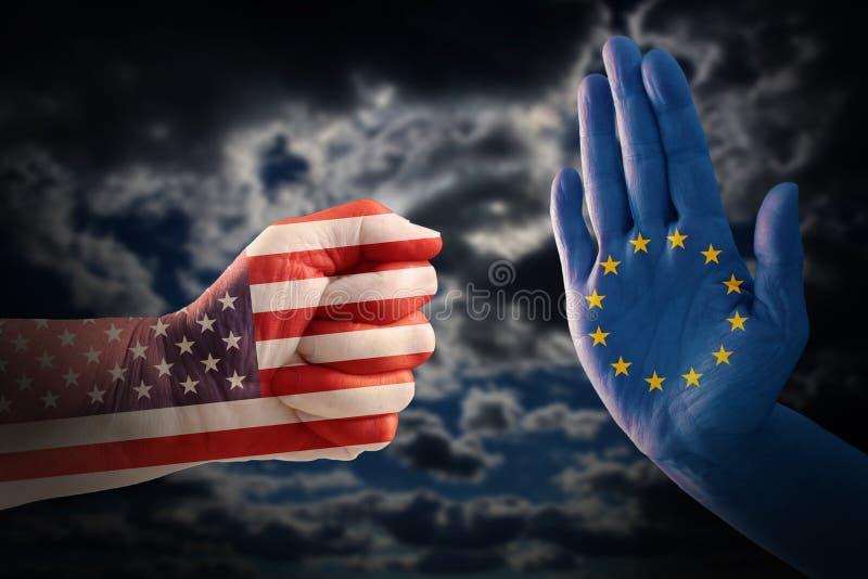 Handla konflikten, näve med USA flaggan mot en hand med europén royaltyfri foto