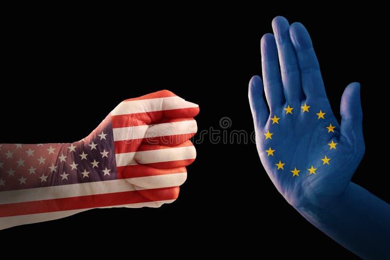 Handla konflikten, näve med USA flaggan mot en hand med europén royaltyfri bild