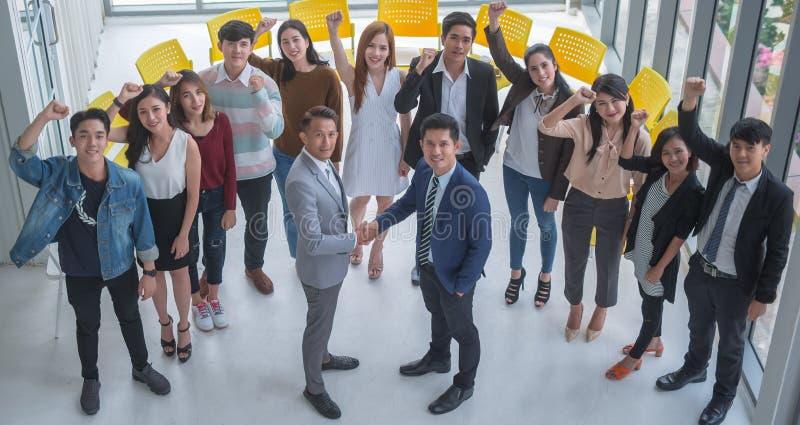 Handla och asiatiskt folk för framgånglag som skakar handen och lönelyfthanden för att fira i regeringsställning royaltyfri fotografi