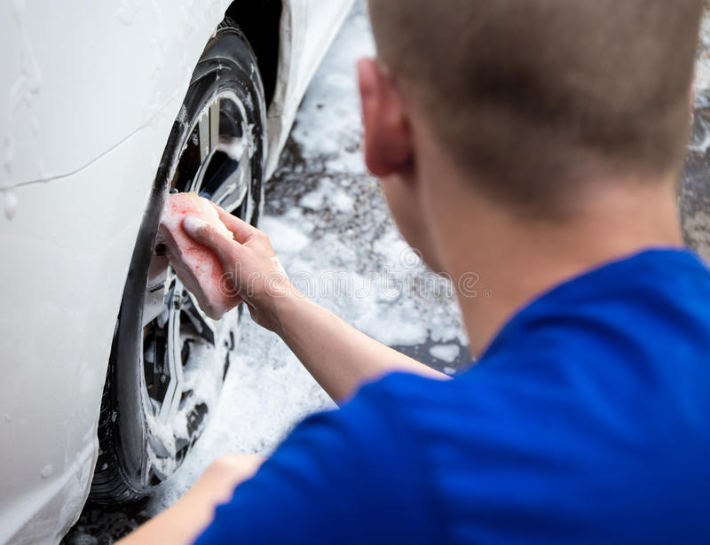 Handle carwash concept - back view of man washing car wheel with royalty free stock photography