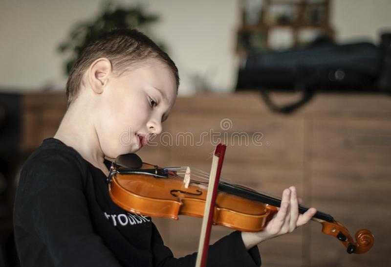 Handle hold violin. Little boy carrying violin. Young boy playing violin, talented violin player stock image
