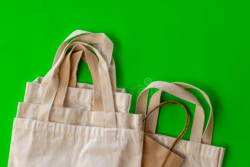 The handle of many cloth bags on the green backdrop. Isolate close-up, background, handle of cloth bags and paper, overlapping on a green backdrop stock image