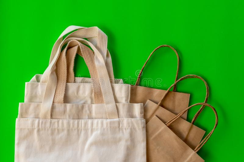 The handle of many cloth bags on the green backdrop. Isolate close-up, background, handle of cloth bags and paper, overlapping on a green backdrop royalty free stock photography