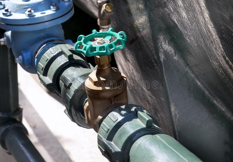 Handle metal gate valve green on the steel pipeline with fitting. S joint with screws and nuts royalty free stock images