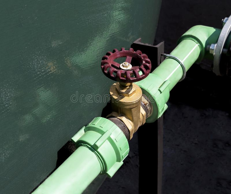 Handle metal gate valve red on the steel pipeline with fittings. Joint with screws and nuts royalty free stock image