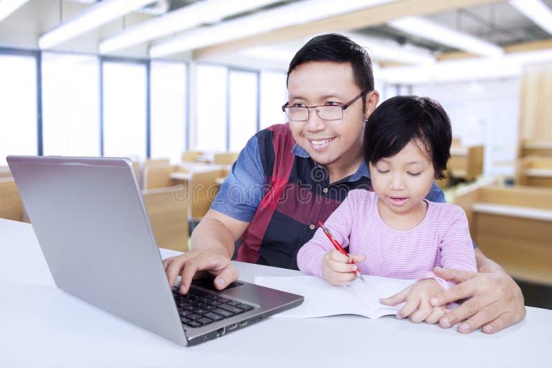 Handleda genom att använda bärbara datorn, medan undervisa hans student arkivfoto
