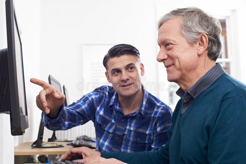 Handleda Helping Mature Man i datorgrupp arkivbilder