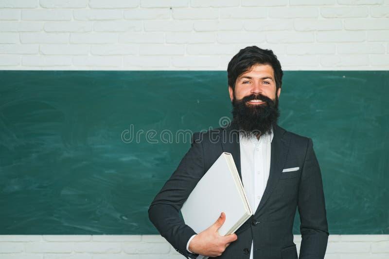 handledning Dra tillbaka till skolan och lycklig tid Sk?ggig professor p? skolakursen p? skrivbord i klassrum Lärare som förbered arkivfoto
