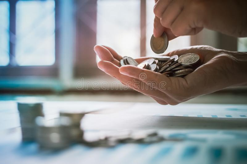 Handles coins placed on a pile of money on the table with light Sunset& x27;s business concept royalty free stock photography