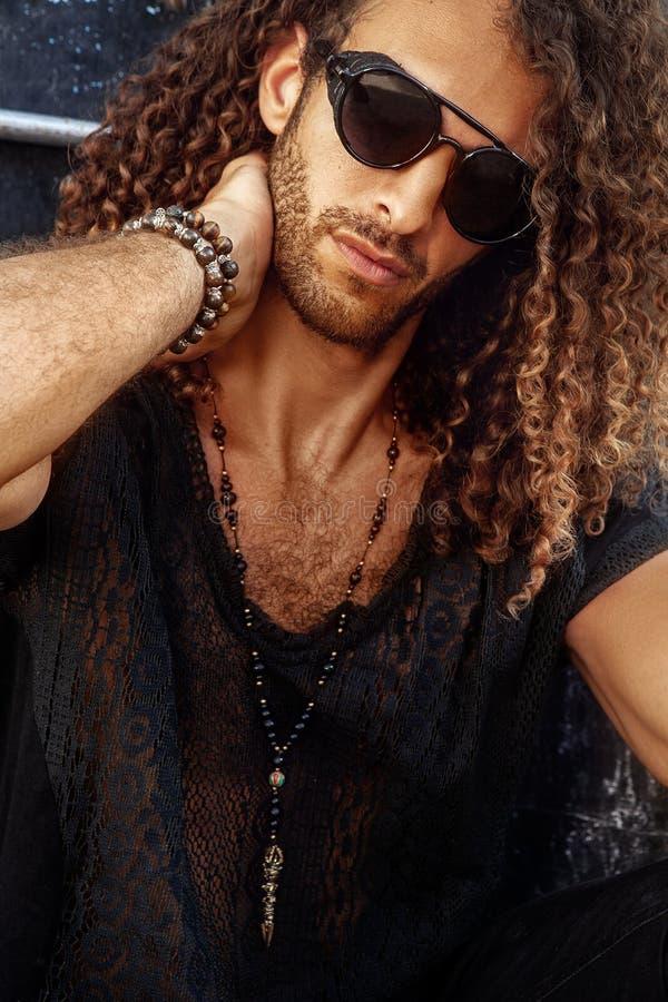 Handlicher Mann mit lockigen Haaren und Schmuck auf den Armen und der Brust, Außenfoto unter der Sonne - Bild lizenzfreies stockfoto