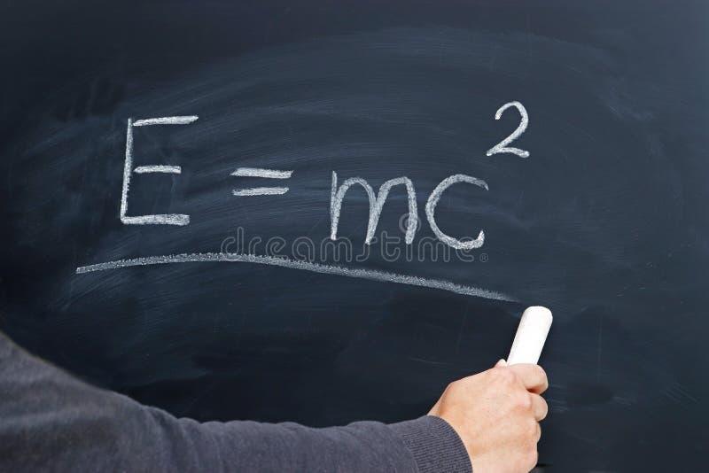 Handling av en ung person som skriver Einsteinformeln på en tavla arkivbilder
