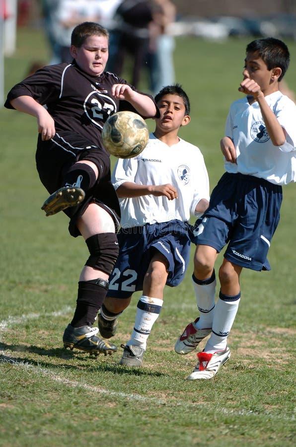 Handling för pojkeungdomfotboll arkivfoton