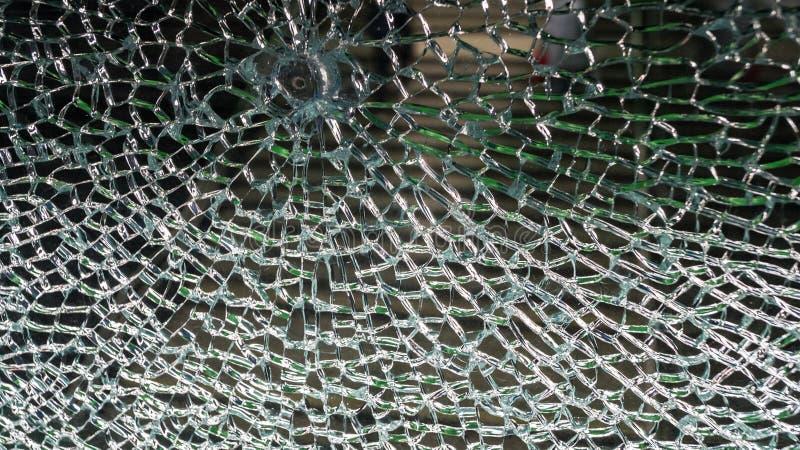 Handlingen av ondsint ligistfasoner broken glasvägg royaltyfri bild