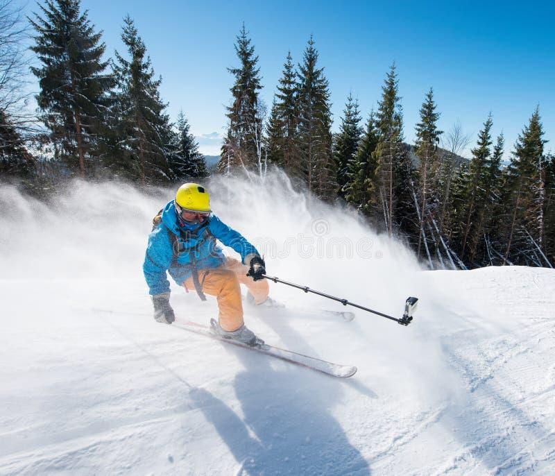 Handlingskott av den yrkesmässiga skidåkaren som tar selfiesfotoet med en kamera på skidåkning för selfiepinnestund arkivfoton