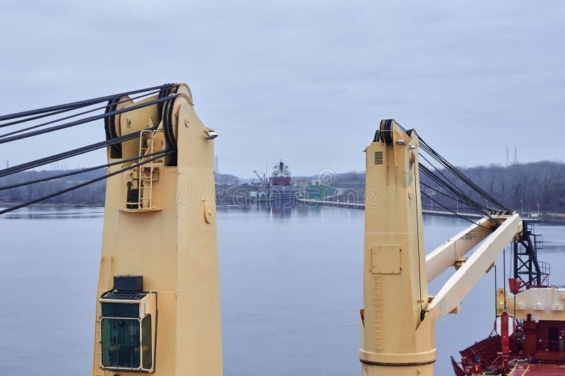 Handlowego statku naczynie z dwa żurawiami przechodzi kędziorki w Wielkich jeziorach, Kanada w zima czasie zdjęcia stock
