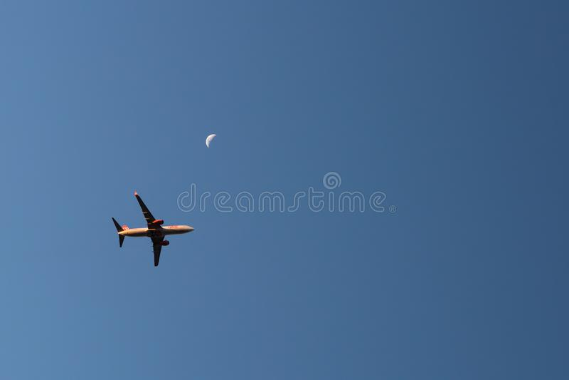 Handlowej linii latający samolot z powstającą księżyc w tle podczas zmierzchu zdjęcia royalty free
