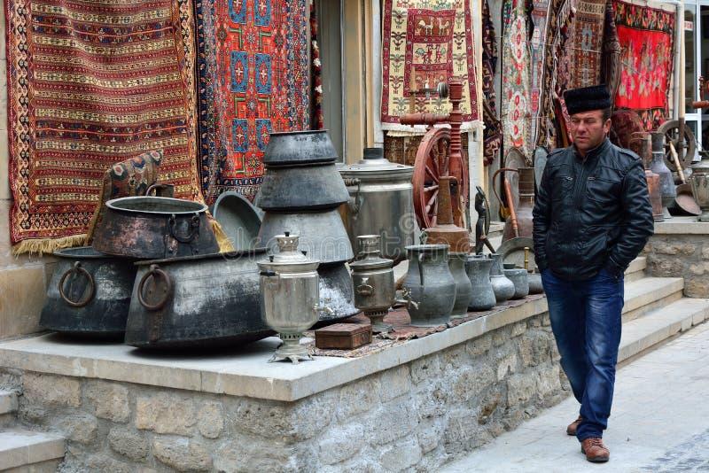 Handlowiec sprzedaje tradycyjnych metali garnki, dywany w Baku Starym mieście i, zdjęcia royalty free