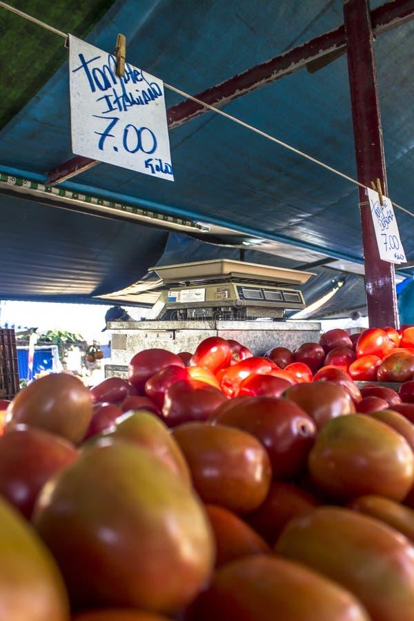 Handlowowie sprzedają świeżych pomidory jako sprzedaże detaliczne konsumenci na ulicznym rynku w Sao Paulo obrazy stock