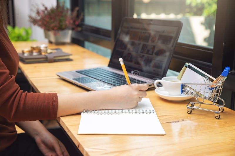Handlu elektronicznego pojęcie, kobiety wybrana rzecz od strony internetowej shoppping online z kartą kredytową i moneta w wózku  obraz royalty free