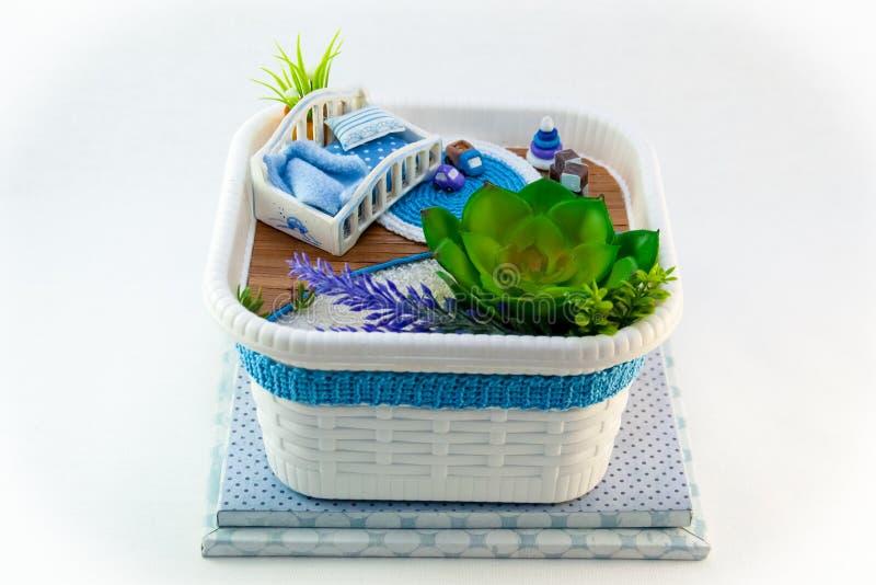Handmädchen, ein blauer Spielzeugraum des Hobbys mit einem Feldbett für Baby stockbild