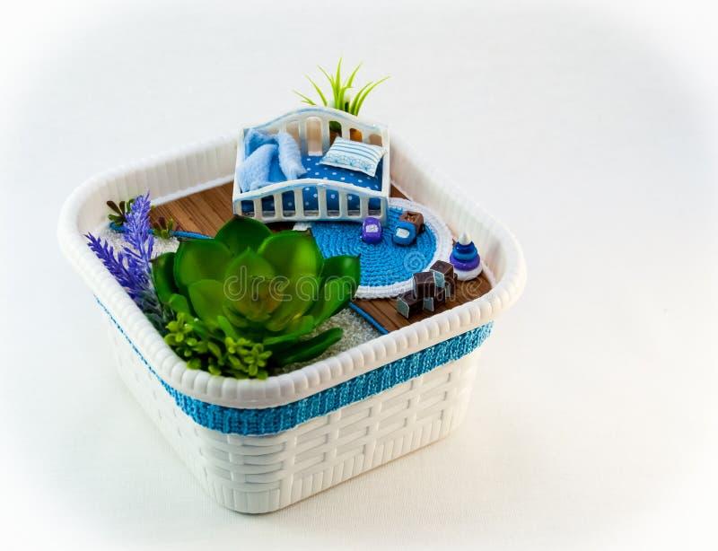 Handmädchen, ein blauer Spielzeugraum des Hobbys mit einem Feldbett für Baby lizenzfreie stockfotografie