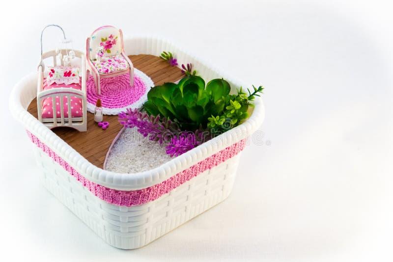 Handmädchen, ein Hobbyrosa-Spielzeugraum mit einem Feldbett für Baby lizenzfreies stockbild