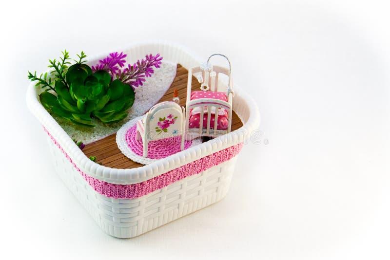 Handmädchen, ein Hobbyrosa-Spielzeugraum mit einem Feldbett für Baby lizenzfreie stockbilder