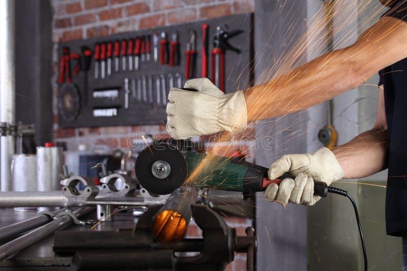 Handmän arbetar i verkstadshuset med metallrör, med byggnadshandskar, med metallskärande skärverktyg, med gnistor och hantverk royaltyfri foto