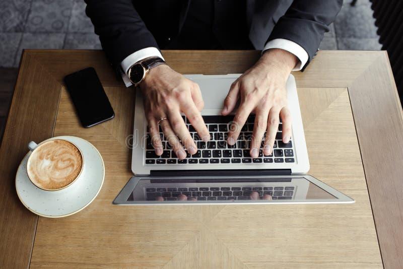 Handmän ligger på bärbara datorn, nära en telefon och en cappuccino royaltyfri bild