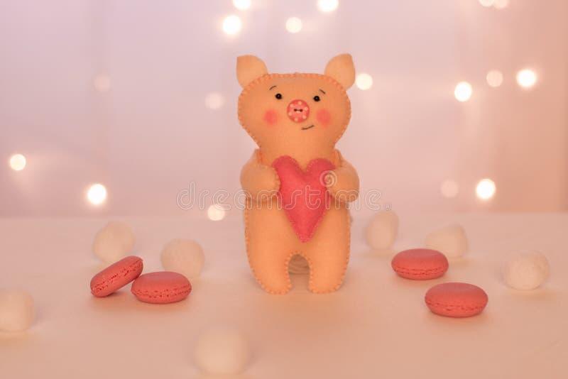 Handmade бежевое piggy сделало войлока с сердцем стоит на предпосылке светов рождества, розовых macarons и мягких шариков стоковое фото rf