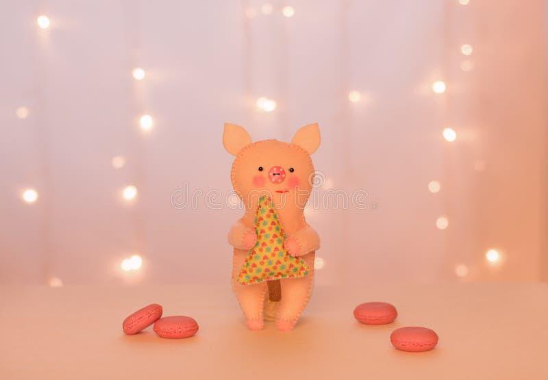 Handmade беж piggy войлока с рождественской елкой стоит на предпосылке светов и розовых macarons стоковое изображение