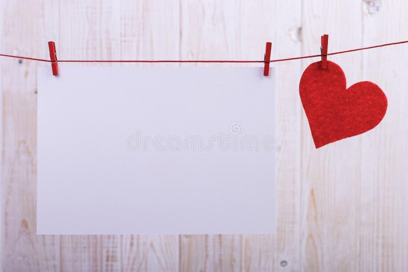 Handmade красные чувствуемые сердца и белая бумага вися на веревочке с зажимками для белья Концепция, знамя, космос экземпляра, ф стоковые фотографии rf
