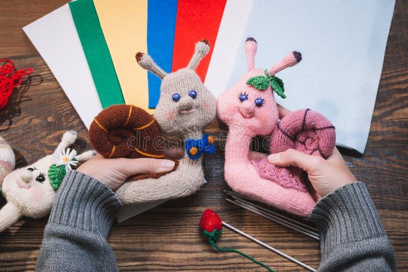 Handmade подарки Делать ручной работы игрушки crochet Связанные улитки на деревянной предпосылке стоковые изображения rf