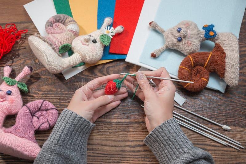 Handmade подарки Делать ручной работы игрушки crochet Связанные улитки на деревянной предпосылке стоковые фото