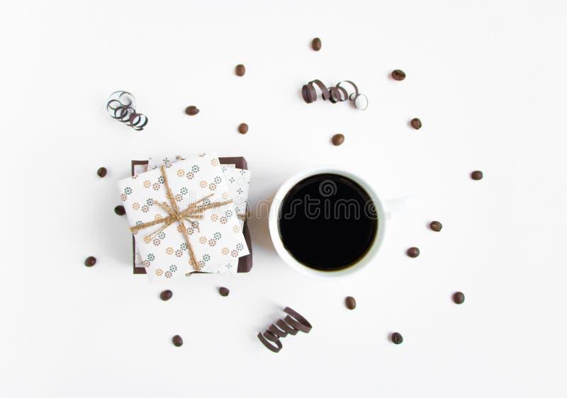 Handmade подарки и чашка на белой предпосылке украшенной с кофейными зернами и бумагой serpentine Взгляд сверху, плоское положени стоковое фото