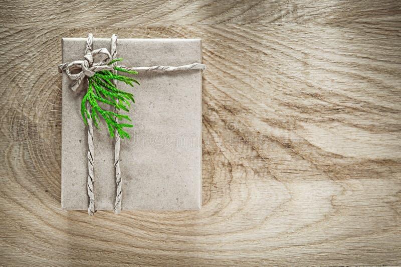 Handmade присутствующая коробка обернутая в коричневой бумаге с зеленой ветвью дальше стоковые изображения rf