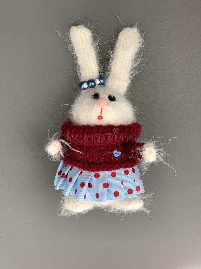 Handmade связанная игрушка Зайчик пасхи в красном свитере с и голубой юбке Игрушка рождества кролика зайцы стоковая фотография