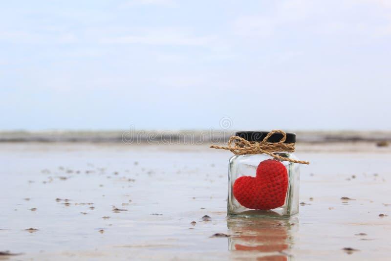 Handmade сердце вязания крючком в стеклянном опарнике на тропическом пляже с красивым голубым небом стоковая фотография