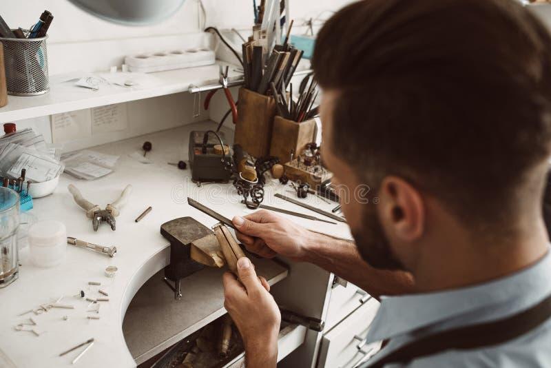 handmade Achtermening die van jonge mannelijke juwelier een ring maken bij zijn werkbank stock fotografie