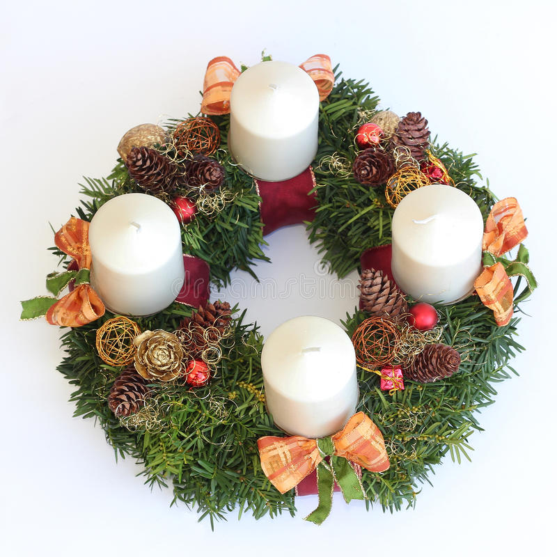 Handmade advent wreath with white candles, cones, orange ribbons. Isolated on white royalty free stock image