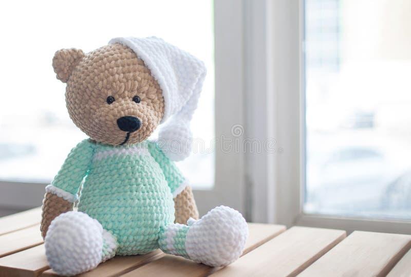 Handmade amigurumi teddy bear on wooden table.  royalty free stock photos