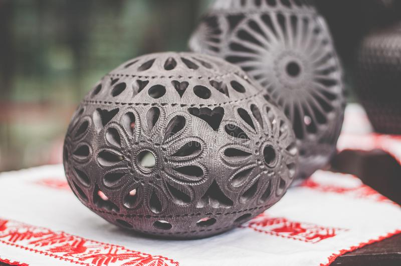Handmade article of black clay. Handmade article made with black clay in oval form and with flower designs royalty free stock photos