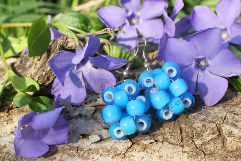 Handmade bead earrings on the nature background. Handmade blue bead earrings with wood violet in spring on the nature background royalty free stock photos