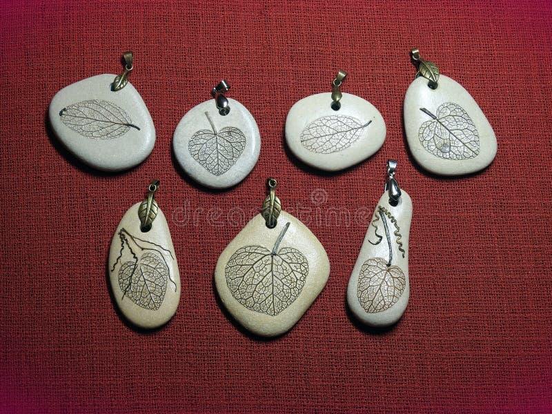 Handmade pendants using sea stone and leaf skeleton, Lithuania royalty free stock photography