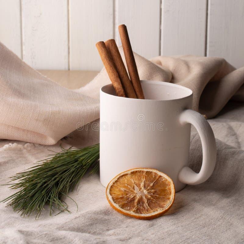 Handmade biała ceramiczna filiżanka, garncarstwo, na tle bieliźniana tkanina z wysuszonymi pomarańczami, zdjęcia stock